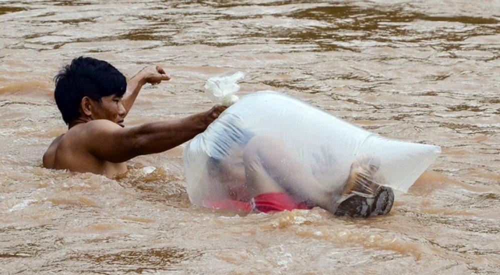 Estudantes são transportados em sacos em rio para não se molharem